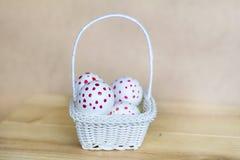 与红色小点的白色复活节彩蛋在小白色篮子 免版税库存图片