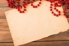 与红色小珠的老葡萄酒纸在木背景 库存照片