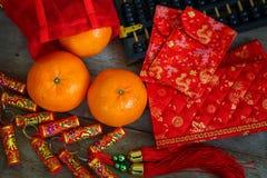与红色幸运的囊和爆竹的桔子 库存照片