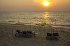 与红色床垫的空的蓝色海滩床在黄沙的绿色黄色机盖下反对有太阳道路的海在 库存图片