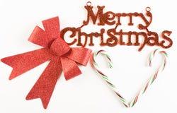 与红色弓和棒棒糖的圣诞快乐标志 免版税库存图片
