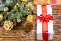 与红色弓的礼物在与欢乐杉木大树枝的表上 库存照片