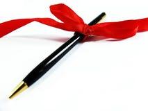 与红色弓的笔在白色背景 免版税库存图片
