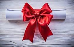 与红色弓的纸卷在木板假日概念 库存照片
