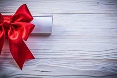 与红色弓的纸纸卷在木板假日概念 免版税库存照片