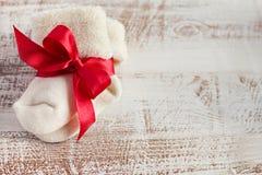 与红色弓的被编织的婴孩袜子木表面上 免版税库存照片