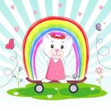 与红色弓的逗人喜爱的动画片猫与在彩虹背景的滑板 免版税库存照片