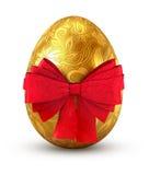 与红色弓的金鸡蛋。 免版税库存图片