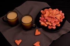 与红色心形的曲奇饼和两个杯子咖啡用牛奶,情人节 免版税库存图片