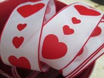 与红色心脏和边界的一条丝带 免版税库存图片
