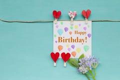 与红色心脏夹子和紫色花的生日快乐卡片 免版税库存图片