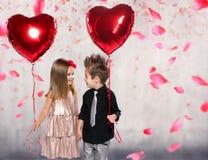 与红色心脏气球的愉快的孩子 免版税库存照片