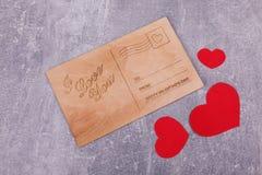 与红色心脏的一张木明信片 免版税库存照片