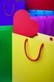 与红色心脏的五颜六色的纸购物袋 图库摄影