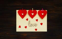 与红色心脏的信封在木背景,华伦泰` s天,顶视图的概念 图库摄影