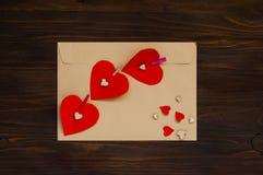 与红色心脏的信封在木背景,华伦泰` s天,顶视图的概念 免版税库存照片