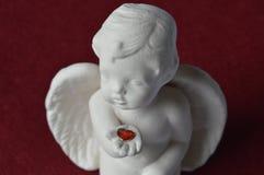 与红色心脏的天使在棕榈 库存图片