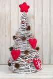 与红色心脏的手工制造圣诞树作为装饰由白色内部的藤制成 库存图片