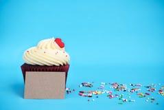与红色心脏的杯形蛋糕,五颜六色洒和棕色笔记 图库摄影