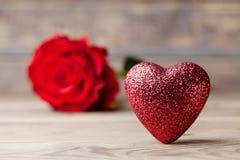 与红色心脏的构成和在葡萄酒木桌上的玫瑰色花 重点 复制文本的空间 图库摄影