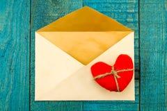 与红色心脏的葡萄酒老信封在蓝色木背景 库存图片