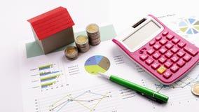 与红色房子和硬币堆、计算器和笔的抵押贷款概念在业务报告 库存照片