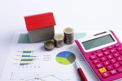 与红色房子和硬币堆、计算器和红色笔的抵押贷款概念在业务报告 库存图片