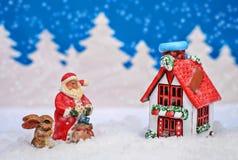 与红色房子的圣诞卡、圣诞老人和兔宝宝和它` s下雪 免版税库存图片
