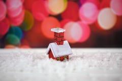 与红色房子的逗人喜爱的小的树装饰的温暖的颜色圣诞节摄影图象雪的与桃红色彩色小灯在背景中 免版税库存照片