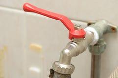 与红色把柄的一个水管插座直角转弯握柄式球形阀水龙头 免版税库存图片