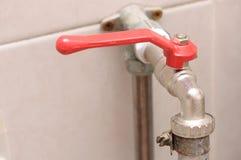 与红色把柄的一个水管插座直角转弯握柄式球形阀水龙头 库存照片