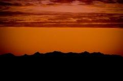 与红色日落的山 免版税库存照片