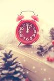 与红色时钟的冬天静物画作为新年、杉木锥体、花楸浆果和被编织的毛线衣的标志 节假日概念 图库摄影