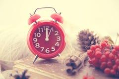 与红色时钟的冬天静物画作为新年、杉木锥体、花楸浆果和被编织的毛线衣的标志 节假日概念 免版税图库摄影