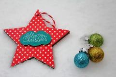 与红色星和五颜六色的装饰品的圣诞快乐卡片 免版税库存图片