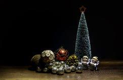 与红色星的高绿色圣诞树在与两个天使的上面和装饰球在昏暗的光 免版税库存照片