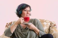 与红色杯子的聪明的成年女性 免版税库存照片
