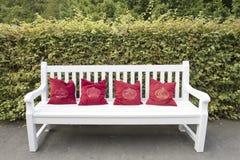 与红色枕头的白色长凳 免版税库存照片