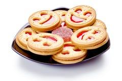 与红色果冻的微笑饼干 背景查出的白色 免版税库存照片