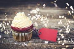 与红色标签的鲜美杯形蛋糕您的在木板的文本的 免版税库存照片