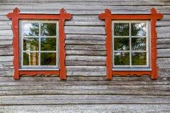 与红色框架在木屋墙壁上,传统风格的两个窗口 免版税库存照片