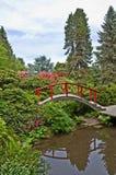 与红色桥梁的美好的日本庭院风景 图库摄影