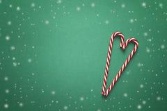 与红色棒棒糖的圣诞节背景以心脏的形式 库存图片