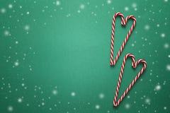 与红色棒棒糖的圣诞节背景以心脏的形式 免版税库存照片