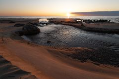 与红色沙子和泉水的美好的日落从退出对海Veczemju Klintis,拉脱维亚- 4月13的河 免版税库存图片