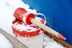 与红色油漆的刷子在冬天背景的白色塑料罐头 免版税库存照片