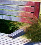 与红色油漆的土气Barnwood长凳在绿草旁边 免版税图库摄影