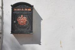 与红色浅浮雕的一个黑葡萄酒金属邮箱在白色墙壁上的中部,一个倾斜的阴影从箱子落 免版税库存照片