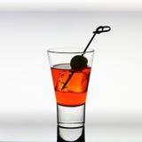 与红色液体,橄榄,冰块的短的饮料玻璃 免版税库存图片