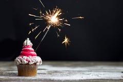 与红色漩涡结霜和闪烁发光物,圣诞节杯形蛋糕的杯形蛋糕 图库摄影